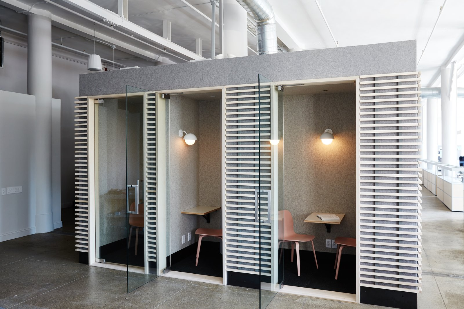 Pink Muuto Visu Chairs invite employees into the phone rooms while Dome Sconces by Allied Maker provide gentle light. The felt-wrapped rooms with bleached plywood slats are one of Murphy's favorite features.  Photo 5 of 12 in Space to Work, Room to Play