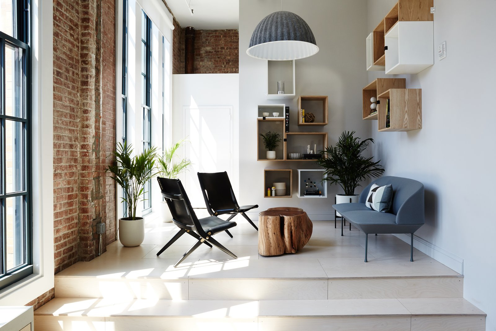 The library features a Muuto Oslo Sofa and Lassen Saxe Chairs. Exposed brick and generous windows are reminders of the warehouse setting.  Interiors from Space to Work, Room to Play