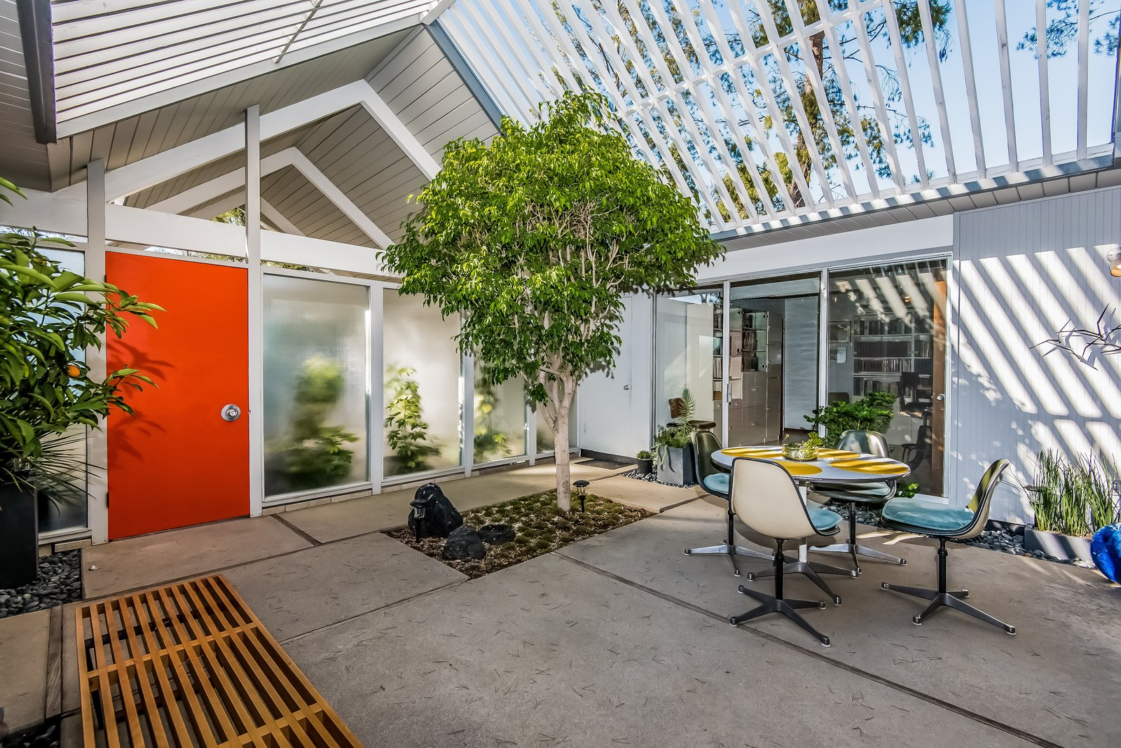A covered entrance doubling as a carport leads to the square atrium, where cutouts in the concrete allow greenery to establish a sense of the outdoors. Enclosed in glass on all four sides, the atrium opens to the living room, multipurpose room, office and retreat.  Photo 3 of 13 in With Only One Previous Set of Owners, a Pristine Eichler Home Asks $799K