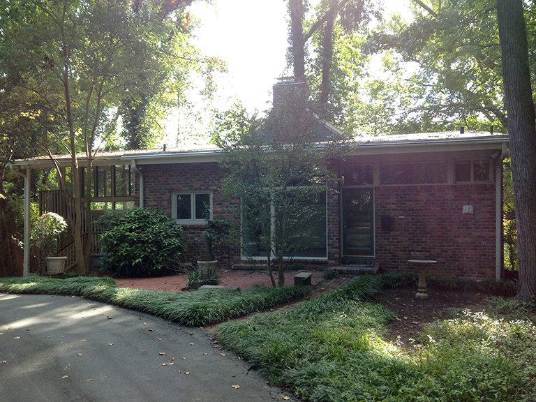 "Architect Janice Finein shared a photo of the residence before the renovation. ""We changed the roof lines, extended the height of the brick wall, replaced the windows and doors, as well as added new materials and details,"" she says.  Photo 2 of 11 in Move Into This Midcentury Modern Revival in North Carolina For $1.2M"