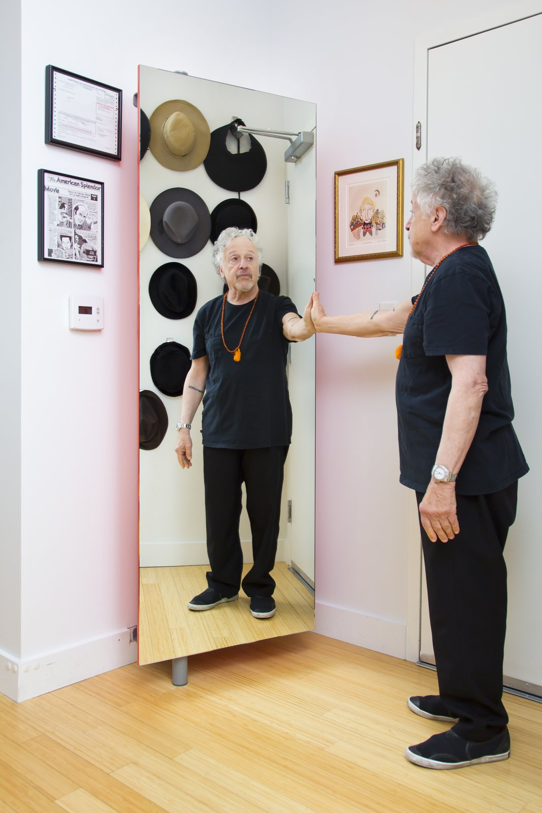Ideal for entries and narrow hallways, the Giralot storage unit swivels open and closed on a wall-mounted column. Here, Alan's shoe rack doubles as a full-length mirror.  Photo 6 of 6 in Two Film Industry Veterans Flip the Script With a Suburb-to-City Move