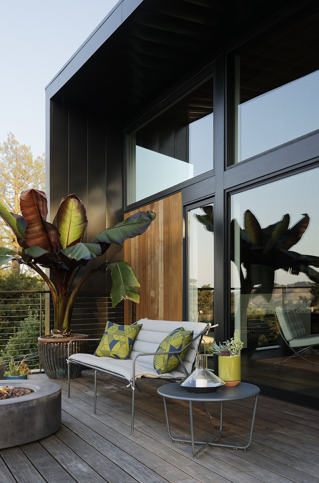 The barware, candle holders, dining set, lantern, terracotta planters, outdoor seating, and side table are all from the Modern by Dwell Magazine collection for Target. The fire pit is from Restoration Hardware.  Photo 1 of 1 in Show Us Your Modern by Dwell Magazine Decor