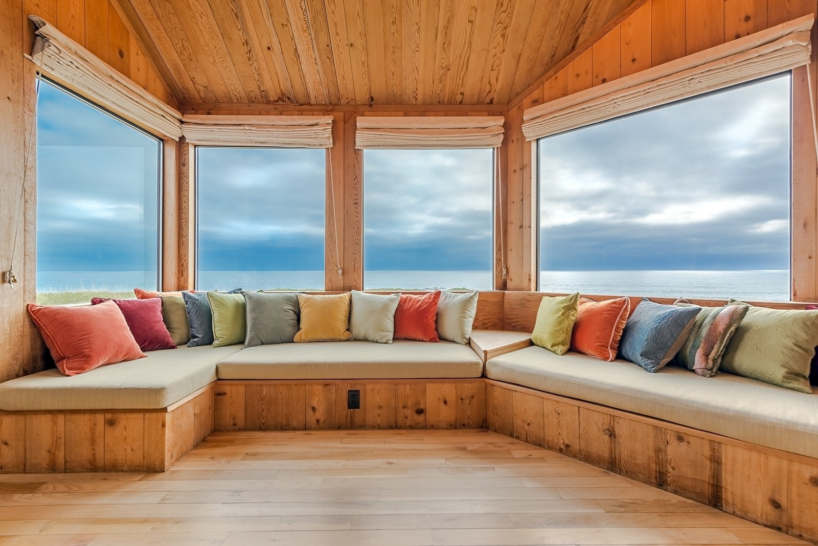 Banquette seating in the living room places guests at the edge of a panoramic view. A 1970s chessboard hides under one of the cushions.  Photo 5 of 12 in Settle in the Celebrated Sea Ranch For Under $2.9M