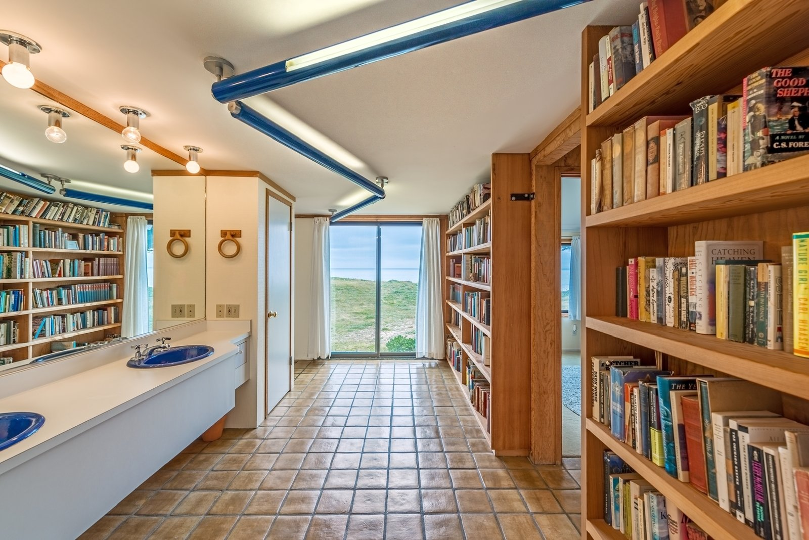 In keeping with Moore's whimsical design sense, a guest bathroom has its own library.  Photo 11 of 12 in Settle in the Celebrated Sea Ranch For Under $2.9M