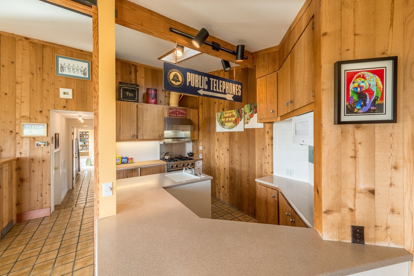 Original wood paneling and tile flooring run throughout the house. The front entry leads into an integrated kitchen and dining space.  Photo 2 of 12 in Settle in the Celebrated Sea Ranch For Under $2.9M