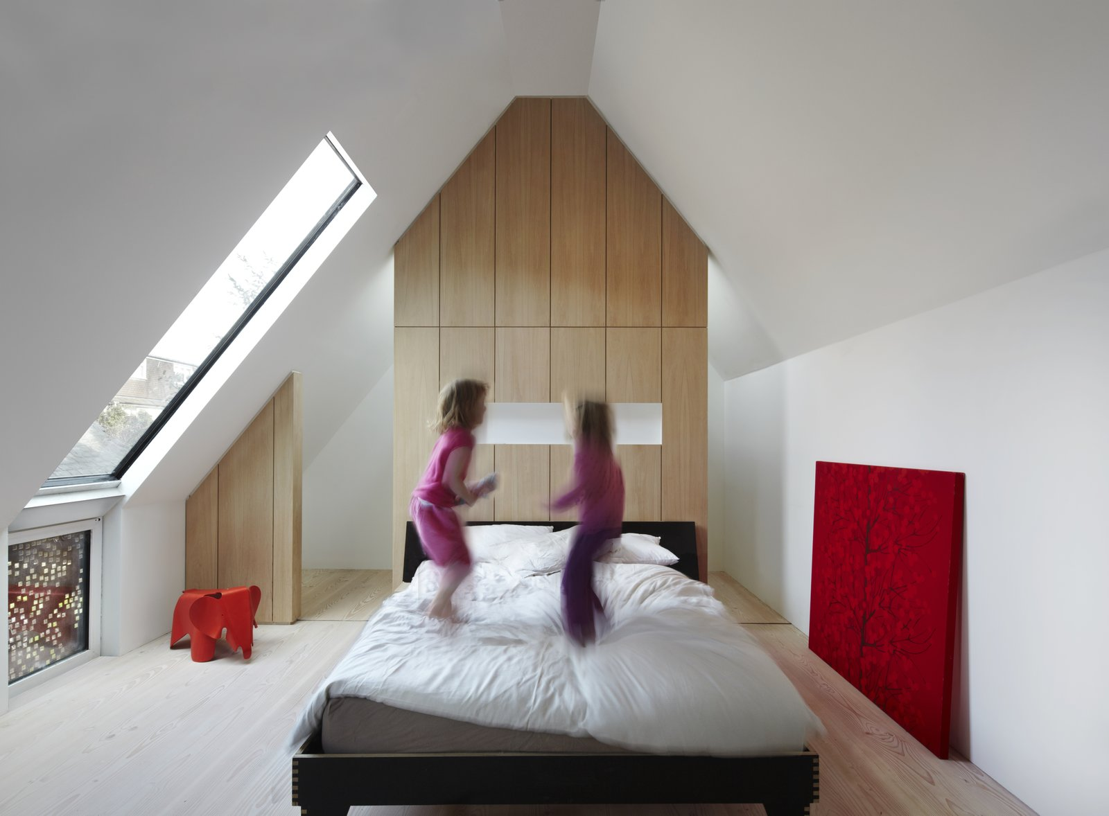 Large windows, partially screened by perforated steel, make for an airy master bedroom, which exhibits more bespoke oak cabinetry.  Photo 8 of 11 in Weathered Steel Clads a $4.7M Home Near London's Kew Gardens