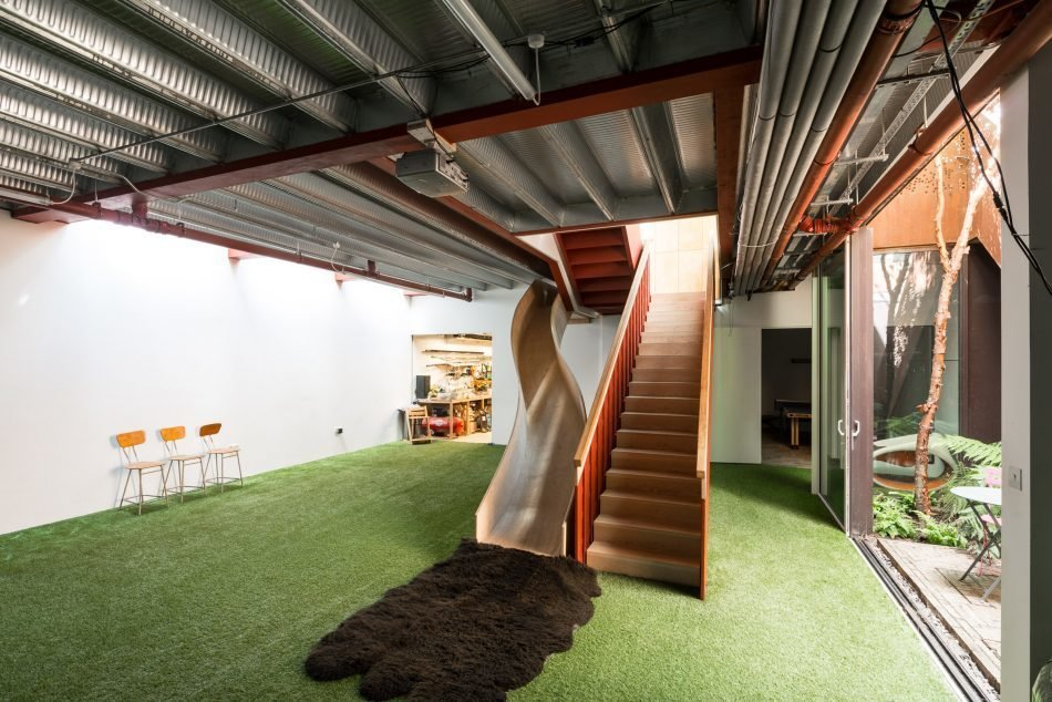 Carpet Floor, Playroom Room Type, and Hallway Alternative routes, levels, and spaces create a landscape of delight in the home—like this slide that leads from the living room to the basement.  Photo 11 of 11 in Weathered Steel Clads a $4.7M Home Near London's Kew Gardens