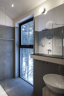 A bathroom and shower overlooks the surrounding forest.