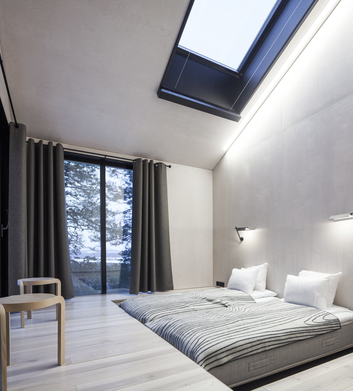 Bedroom, Bed, and Light Hardwood Floor The bedrooms are placed on opposite ends of the cabin, each equipped with sliding doors that lead to the netted terrace. Above, skylights offer additional views of the stars.  Photo 6 of 8 in Go Stargazing in Snøhetta's Towering Addition to Sweden's Treehotel