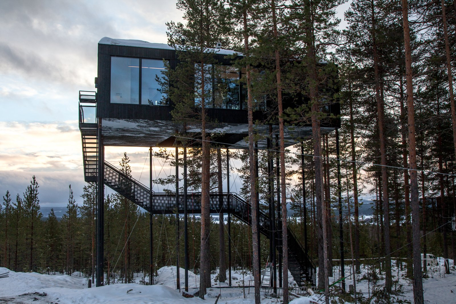 Exterior, Metal Siding Material, and Cabin Building Type Guests ascend a staircase into the cabin, while a small lift carries up their luggage.  Photos from Go Stargazing in Snøhetta's Towering Addition to Sweden's Treehotel