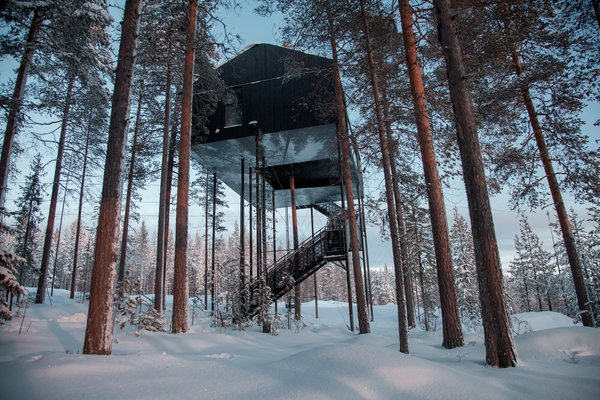 The 7th Room is a remarkable accommodation at Sweden's Tree Hotel that blends into its natural surroundings with a stark black facade. Snøhetta designed the structure, which features an expansive, black-and-white mural of the tree canopy stretched across its base. You can sleep in the beautiful cabin—or if you are brave, under the stars in a giant lofted hammock slung between the two bedrooms.