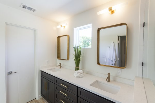 The master bathroom features brass mirrors, light fixtures, and hardware, taking visual cues from the brass accents found in the kitchen.