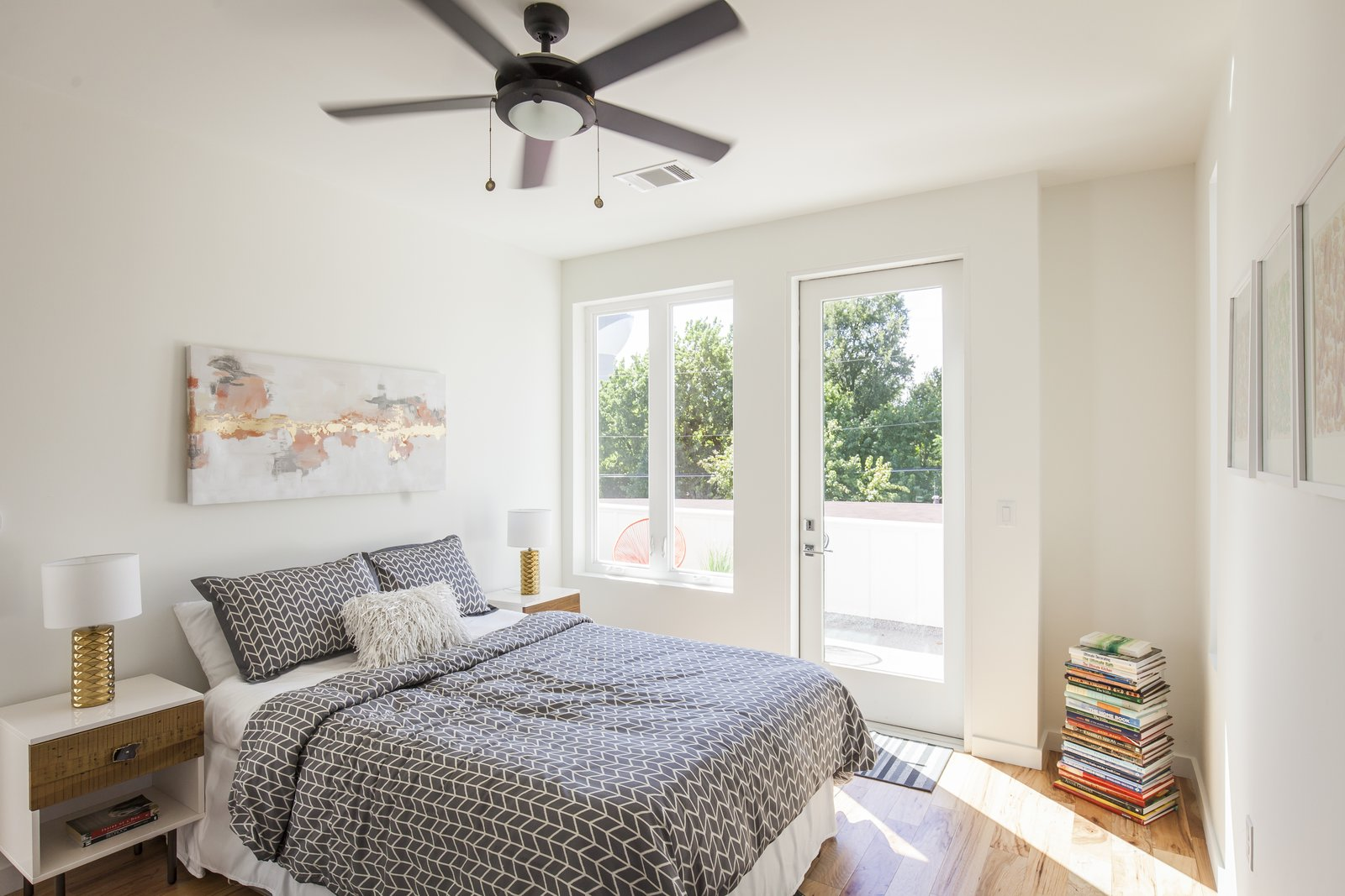 Unit B bedroom with medium toned hardwood floors and bed with chevron bedspread under ceiling fan.