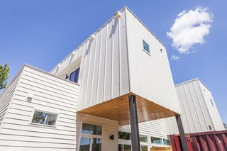 Rios asked architect Reynolds to derive a design from the shipping containers. The duplex takes the shape of stacked volumes clad with vertical and horizontal Hardie boards. The covered patio features clear-coated cedar wood.