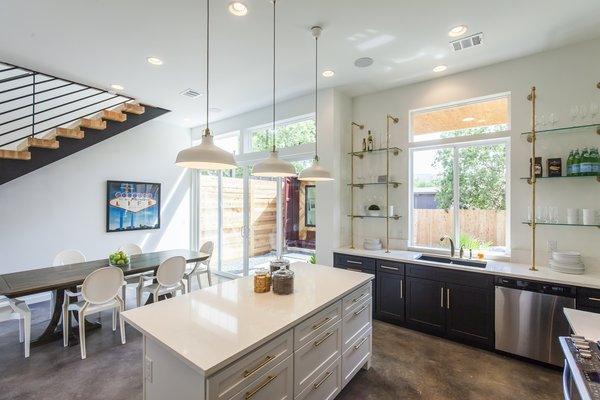 Rios describes Unit B as the more feminine of the two units. Here, black and white cabinets feature a glint of brass hardware. Made of brass galvanized pipe and glass, the shelves by the kitchen sink combine aesthetics and function.