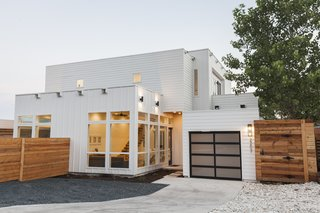 The modular appearance of the duplex, clad in white Hardie plank siding, mimics the look of a two-story container home. With large windows and 11-foot-tall ceilings, the two-bedroom, three-bath residence feels more spacious than its 1,484 square feet. On the ground floor, the living, dining, and kitchen areas flow into one another; potential guests in the shipping container also have easy access to a full bath of their own. A steel-and-wood floating staircase leads to the second floor, which holds two bedrooms with patio access.