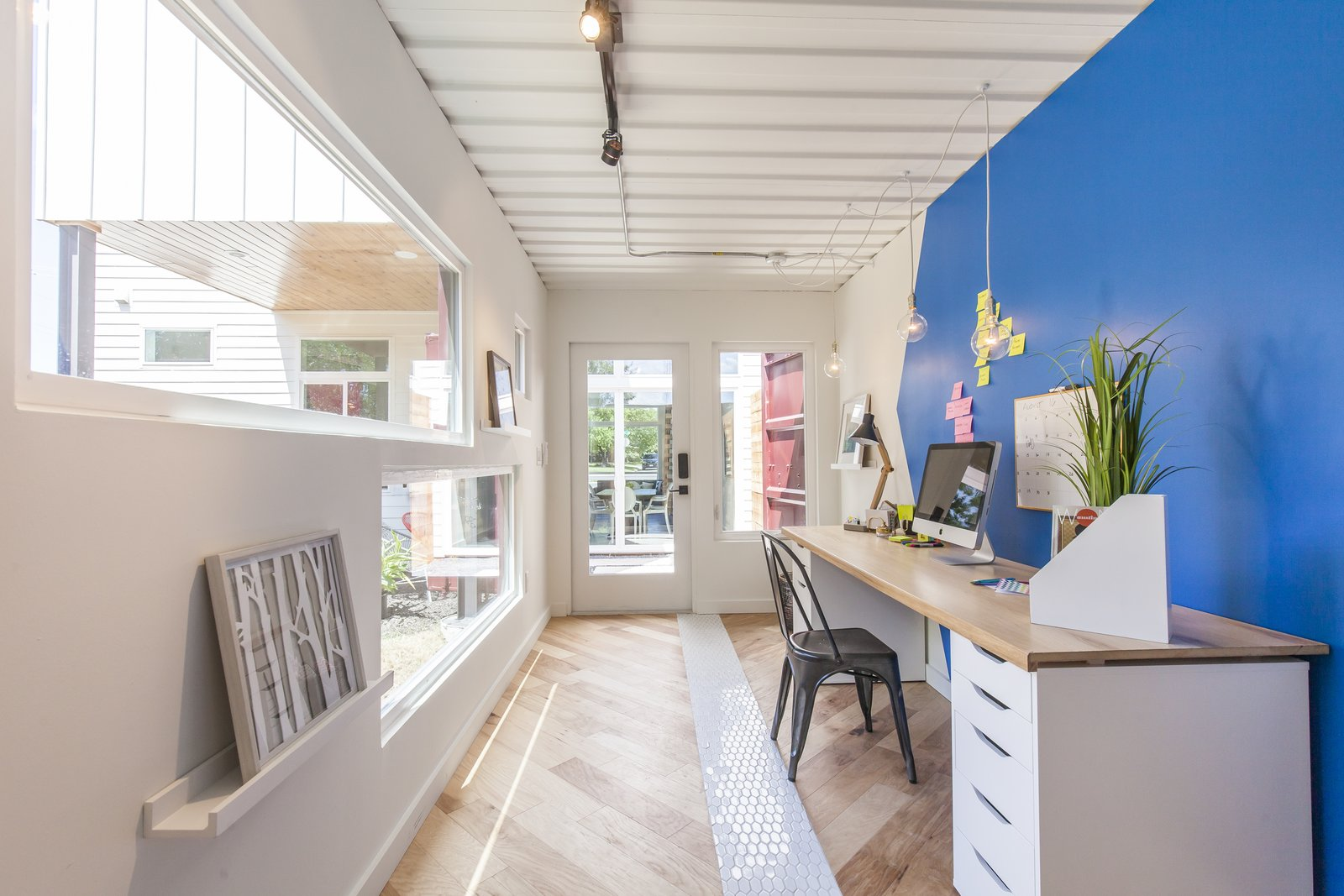 It's up to the homeowner to decide what to do with the additional 160 square feet; here, it's staged as an office. The shipping container features track lighting, wall sconces, a full-height cabinet to hang clothes, and a mini split air conditioner. The floors are a mix of engineered wood and hand-painted tile from Clay Imports. From inside the container, you can see through to the front of the house.  Photo 10 of 10 in Ship Shape: An Austin Home With a Shipping Container Addition Asks $499K