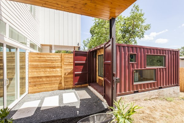 The two units in the duplex share a wall in the main house, so Rios continued the mirrored effect by placing the shipping containers side by side about 10 feet away from the home. Cut into the sides, the windows allow natural light to illuminate the shipping container and are designed to give parents a view of the kids playing in the backyard.