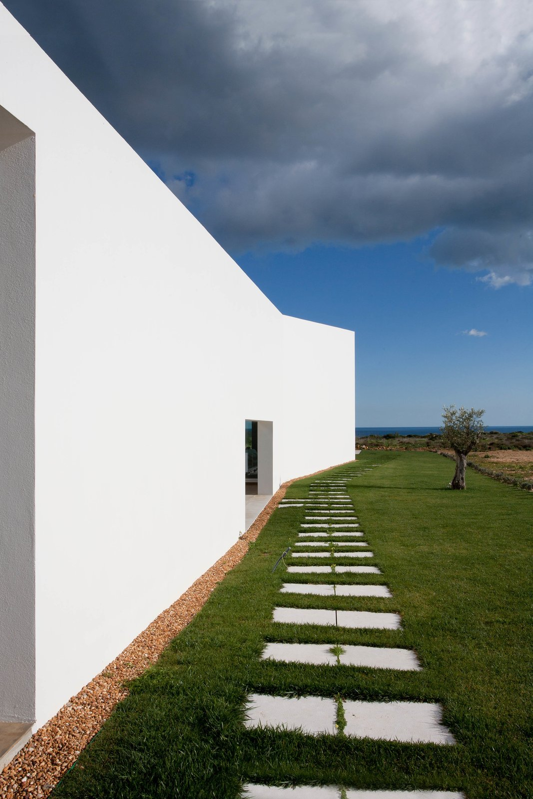 The shape of the home flares towards the front of the lot, expanding from private to public space.  Photo 8 of 9 in Make This Seaside Villa in Southern Portugal Your Own Private Resort For $2M