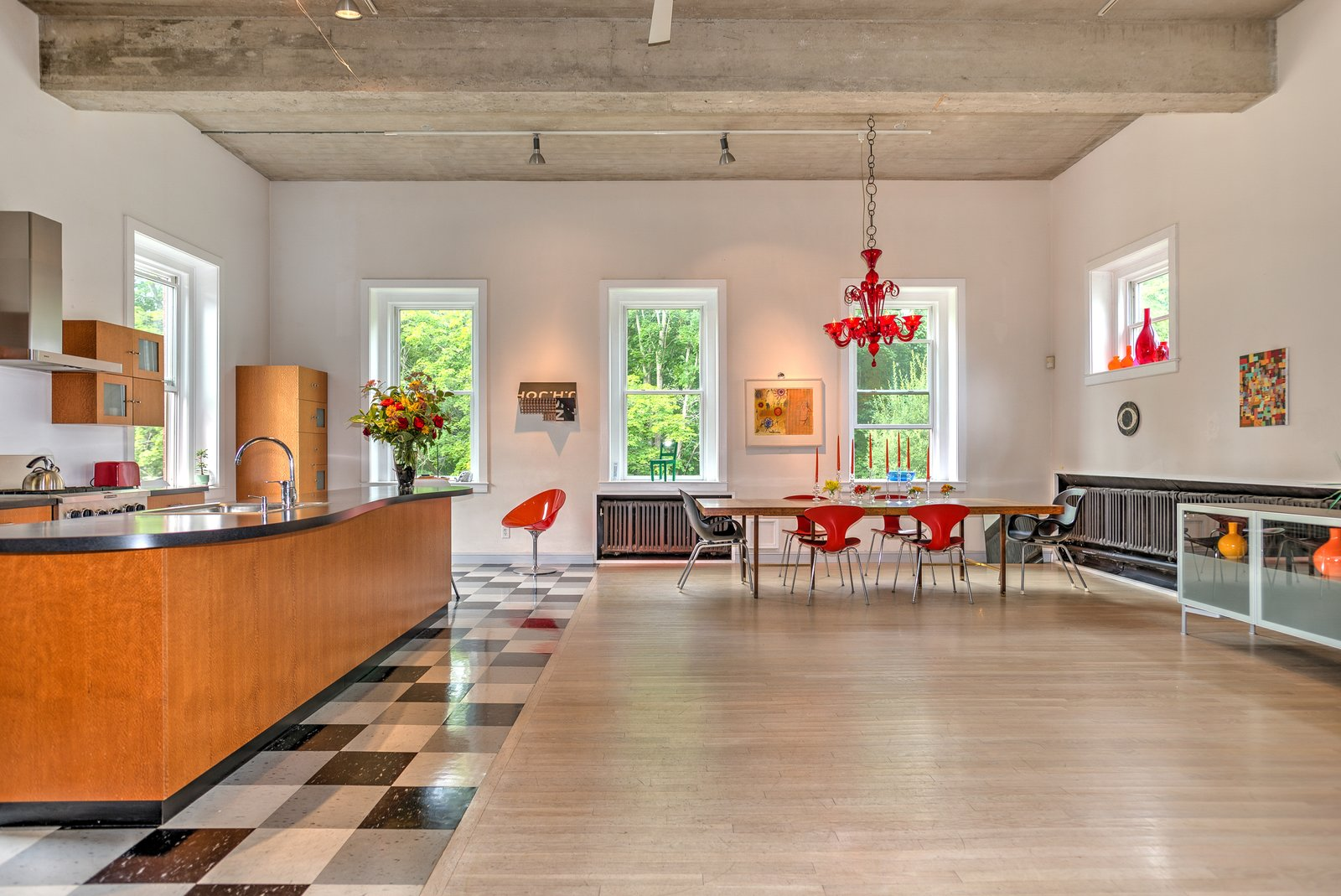 The first floor holds an integrated living room, dining room, and kitchen. When Reed and Blackburn bought the firehouse, the concrete floors were stained with oil from the firetrucks, so they laid stained white oak flooring. They also sandblasted the ceiling to its original concrete finish. A red Murano glass chandelier hangs over a vintage Danish dining table and Bernhardt Design Orbit chairs.  Photo 2 of 9 in A Converted Firehouse Fit For an Artist Is Listed at $749K