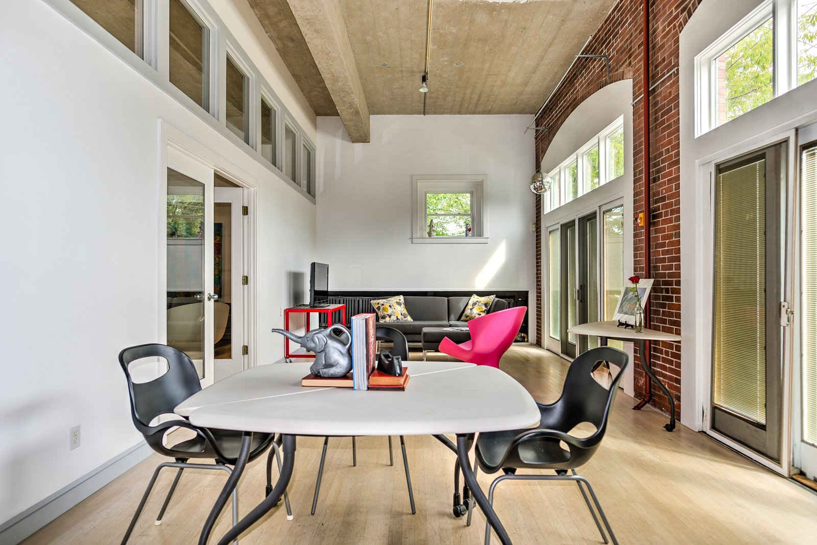 Towards the front of the house, where the original garage doors have been replaced by French doors and transom windows, is a multifunctional space with brick walls that currently functions as an office.  Photo 5 of 9 in A Converted Firehouse Fit For an Artist Is Listed at $749K