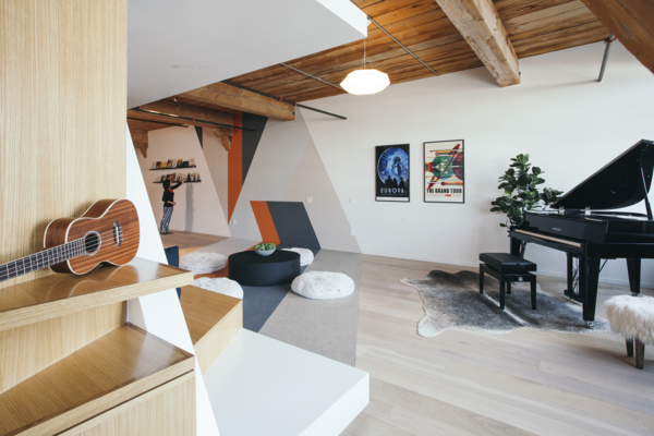 In playful mashup of 3D and 2D elements, a wall mural echoes the FLOR carpet tiles that accent the natural oak engineered flooring.  Photo 4 of 10 in Step Inside One Couple's Game-Changing Live/Work Loft