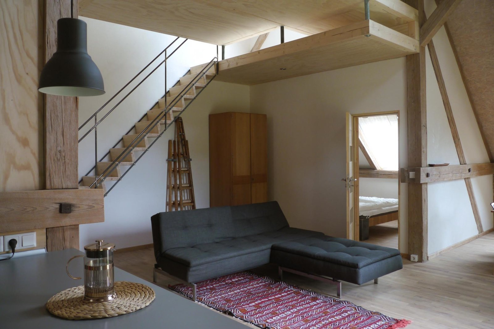 Built in the haylofts of former stables, three loft-style apartments with ample windows and clay plaster walls each have their own personality. Stable North, pictured above, sleeps two in the bedroom and two others in a mezzanine space.  Photo 2 of 10 in Rescuing a Historic Homestead, Two Artists Create a Rural German Retreat