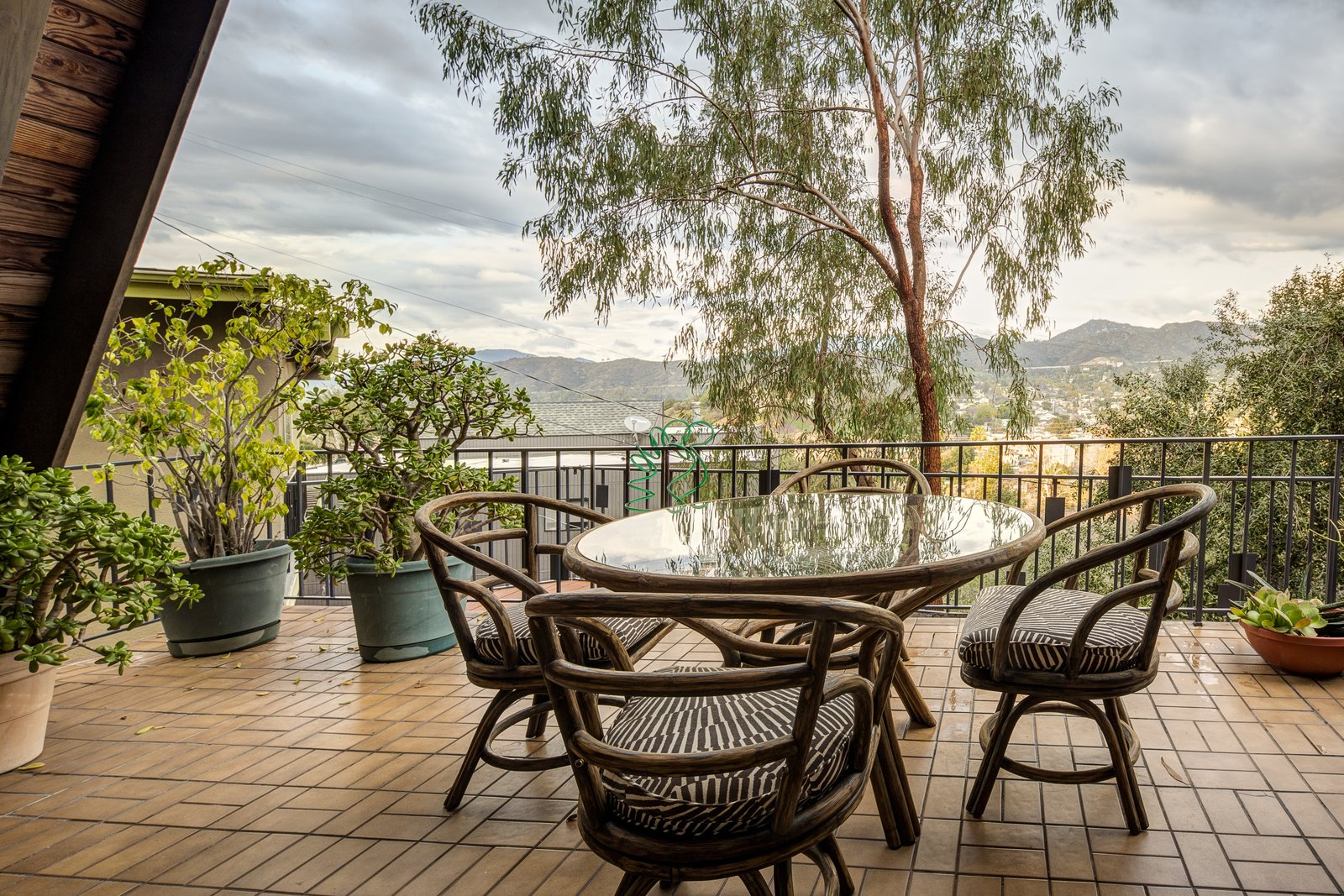The semi-sheltered terrace allows for outdoor dining with views of the surrounding neighborhood and nearby mountains.  Photo 6 of 10 in A Modified A-Frame Overlooking Los Angeles Starts at $699K