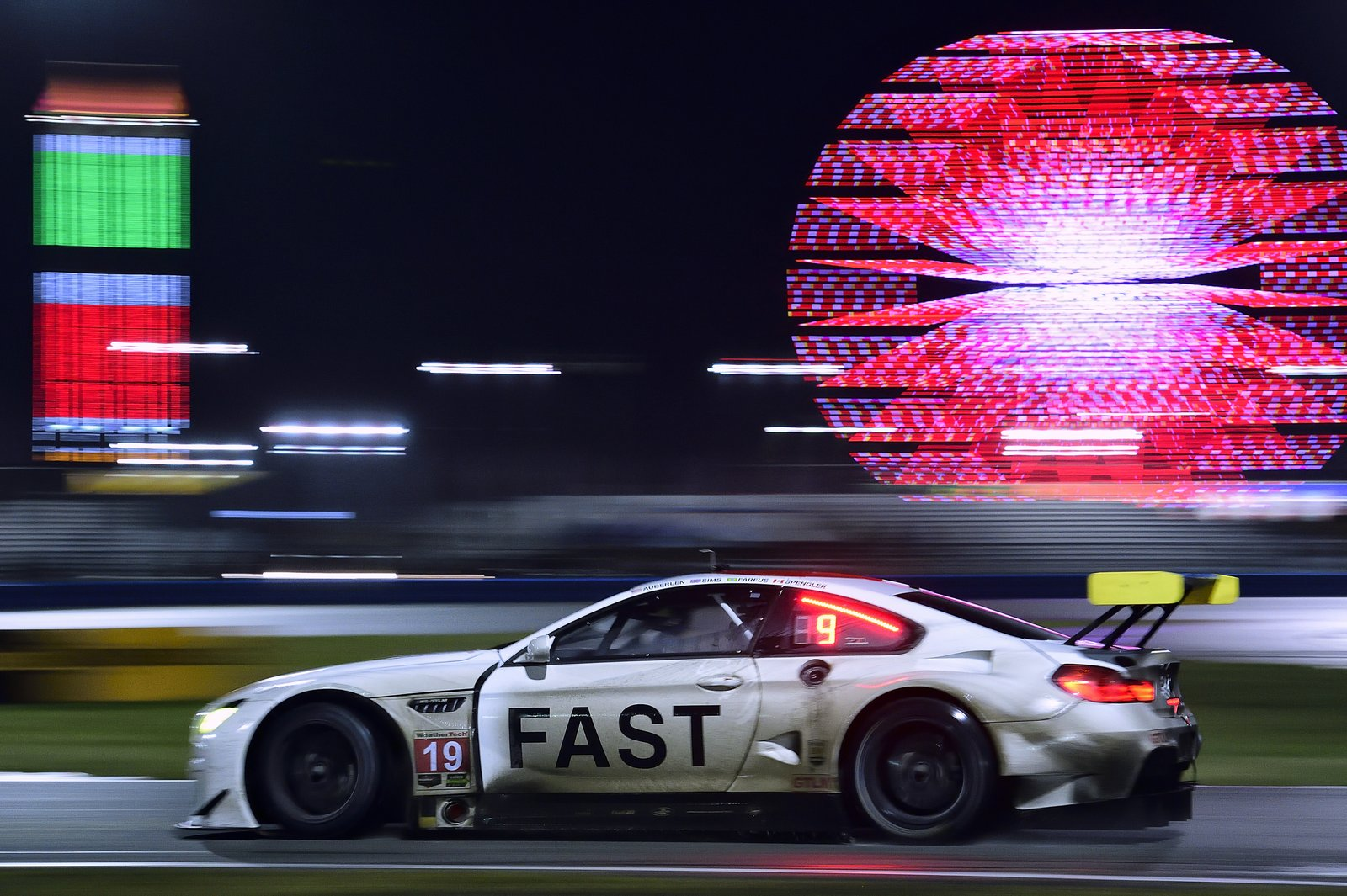 Night falls, the track is slick with rain, and the atmosphere of the infield grows more delirious as fans stay up to watch the race unfold.  Photo 10 of 12 in John Baldessari Blazes a Trail at the Daytona International Speedway With BMW Art Car #19
