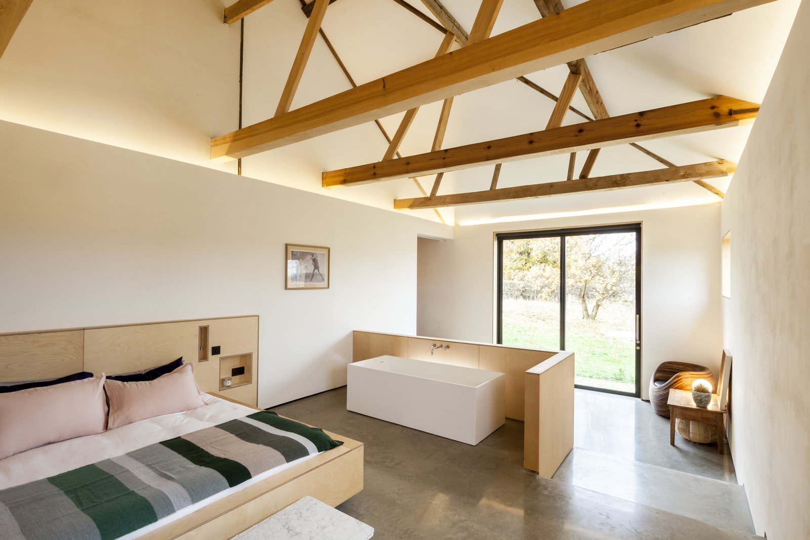 In a life-changing move, homeowners Hannah Smith and Jeremy Witt reside in a caravan in the rural landscape of Suffolk, England, to oversee the restoration of a crumbling barn complex. Simple plywood, cut out to allow views of the landscape, creates subdivisions within the home for private bedroom and bathroom spaces. Rather than formal rooms, they have the effect of large-scale furniture. The master bedroom features an ensuite tub.