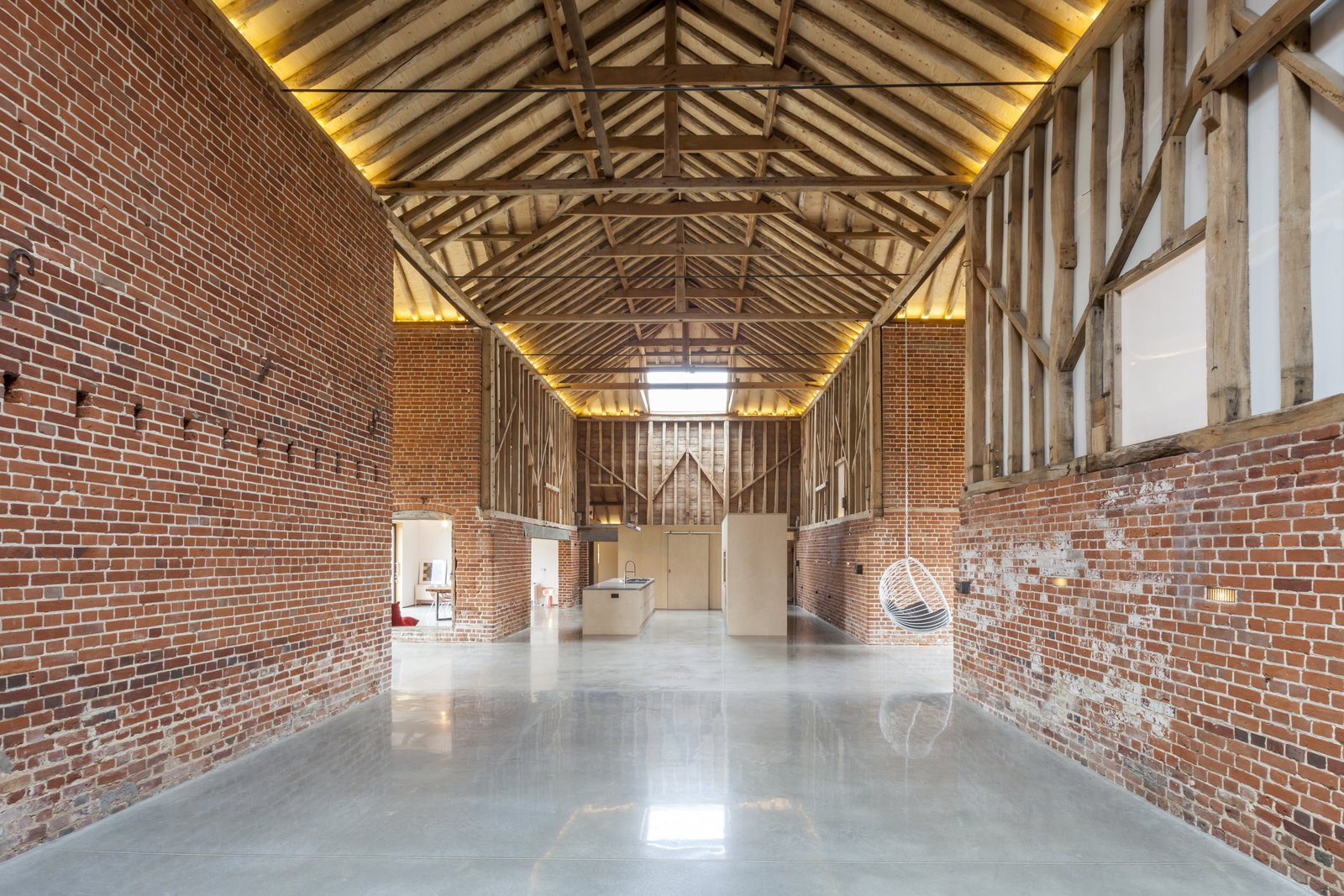 The renovation honors the grand, cathedral-like proportions of the original barn. In addition to the Tagged: Hallway and Concrete Floor.  Photo 4 of 10 in This Converted Barn in the English Countryside Stays True to its Historic Roots