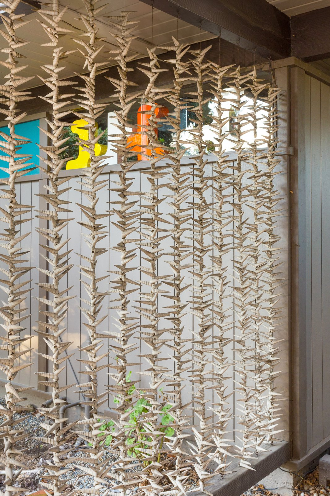 Strung seashells make up an organic screen for the carport, a natural touch added by the seller.  outdoor spaces from Snag This Midcentury Stunner in Southern California For $799K