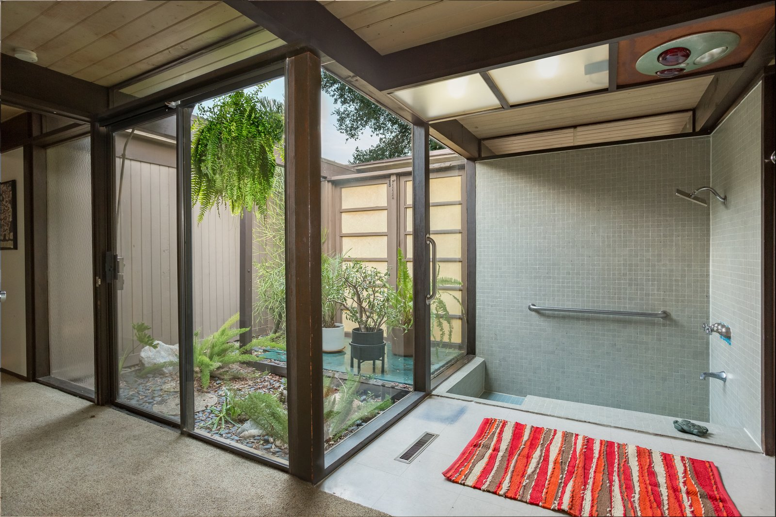 The sunken tile tub and shower in the ensuite master bathroom enjoys an outdoor connection in the form of a small atrium.  Photo 11 of 11 in Snag This Midcentury Stunner in Southern California For $799K