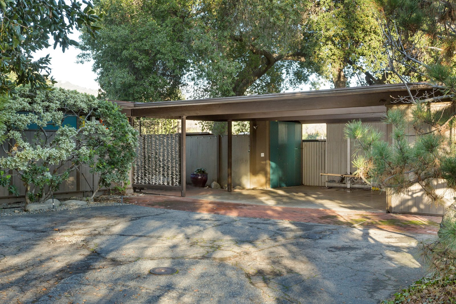 Set back from the street, the home provides privacy and seclusion. At the entrance, a carport leads to a brick-paved walkway that stretches to the front door.  Photo 2 of 11 in Snag This Midcentury Stunner in Southern California For $799K