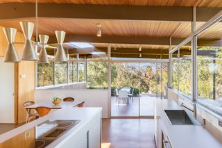From the kitchen, you step out onto a side patio, which has an opening cut into the roof to allow sunlight to fall on a planter. The previous owners, in an attempt to remodel the house in the Spanish style, had gutted the kitchen. Eric Lamers rebuilt the space with cabinetry based on elevation drawings found in Neutra's