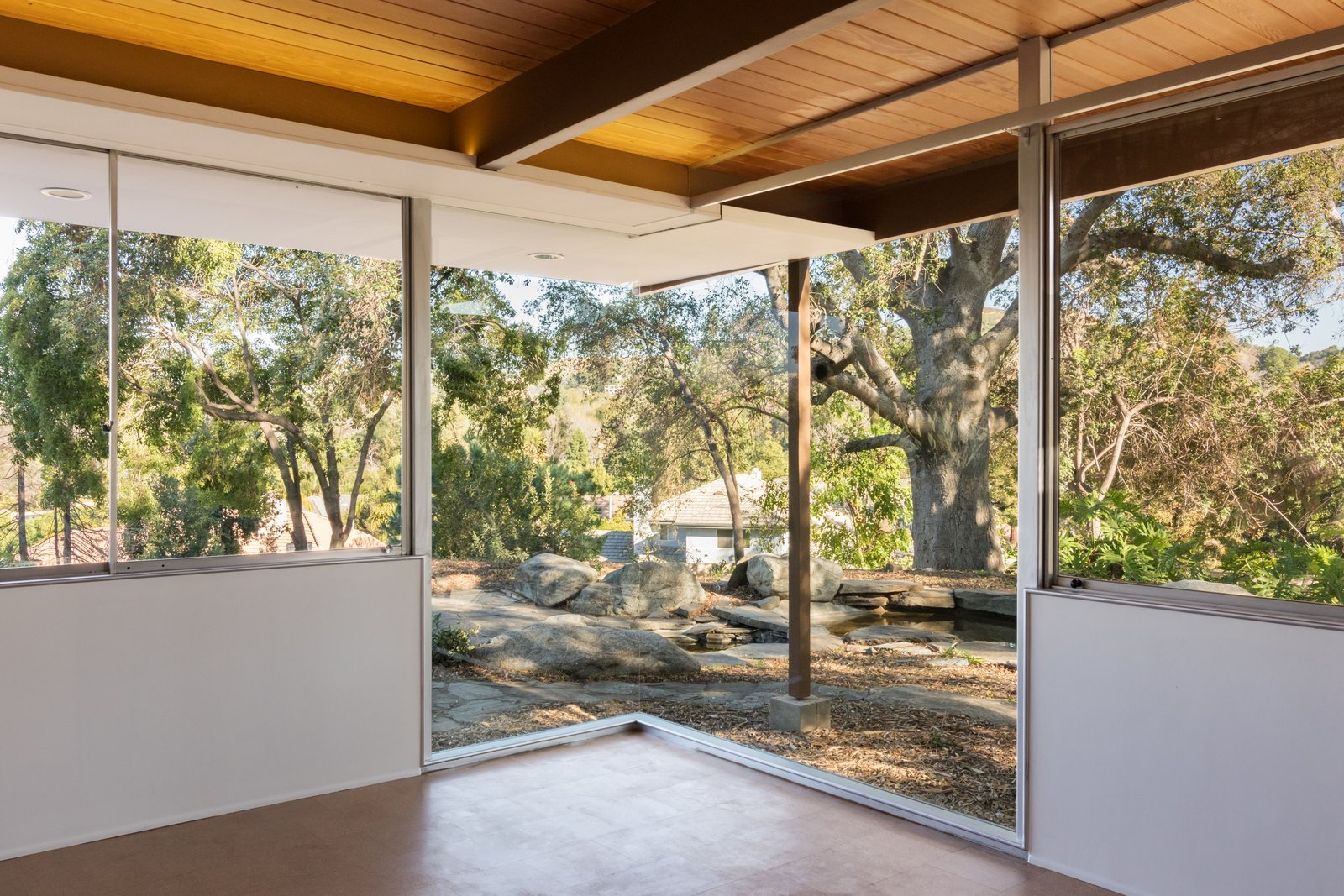 Outdoor, Side Yard, and Trees Situated on the eastern end of the residence, the master bedroom boasts a mitered glass corner window that overlooks a koi pond and a Live Oak tree.  Photo 6 of 9 in Nearly Slated For Destruction, a Restored Neutra in West Covina Asks $1.8M