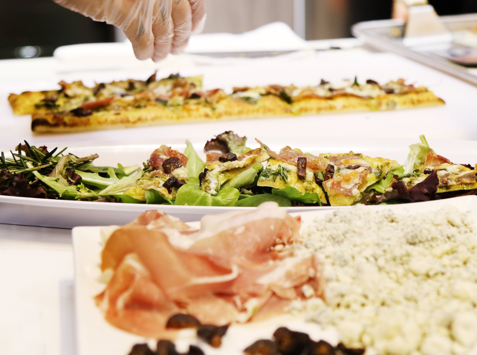 Flatbread topped with prosciutto, stilton cheese, figs, and arugula was part of the menu at Signature Kitchen Suite's impressive 4,000-square-foot exhibition booth.  Photo 8 of 8 in Signature Kitchen Suite's Modern Pavilion Shines at KBIS
