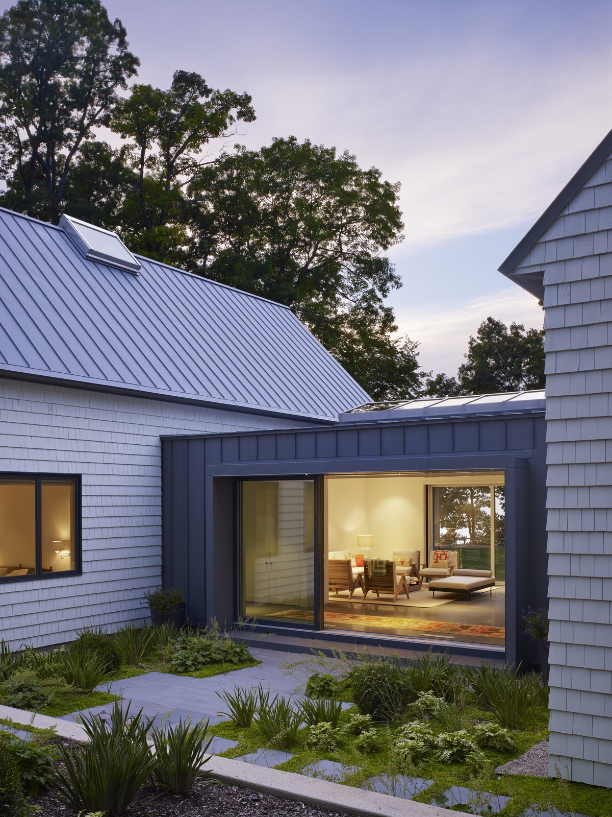 A lushly landscaped bluestone terrace leads guests to the dining porch, which benefits from two LaCantina Multi-Slide Doors that measure 18 feet wide and nine feet tall.  Photo 2 of 7 in Cabins and Connectors Form a Family's Lake Michigan Retreat