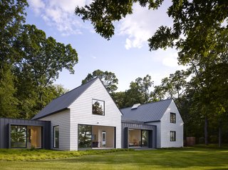 The simple form of each volume is a nod to regional architecture, while durable materials such as white cedar and zinc contribute to a low-maintenance vacation home. The windows and doors feature a bronze anodized aluminum finish on the exterior.