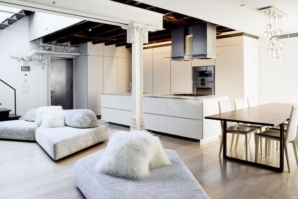 Light Hardwood Floor The minimalist, open kitchen was built into freestanding millwork walls. Valgora strove to layer design elements from the 19th, 20th, and 21st centuries.  Photo 3 of 10 in A Rooftop Addition on a 19th-Century Building Suits a Growing Family's Needs