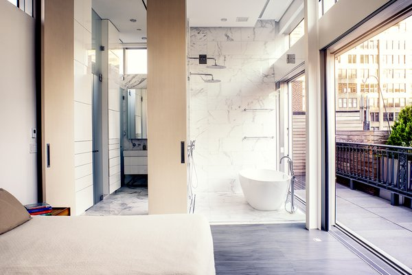 A marble wet room features a freestanding tub by Victoria and Albert and dual showers, while another shower on the terrace offers the option of washing outdoors. A 12-foot wooden door swings back to reveal a dressing room.