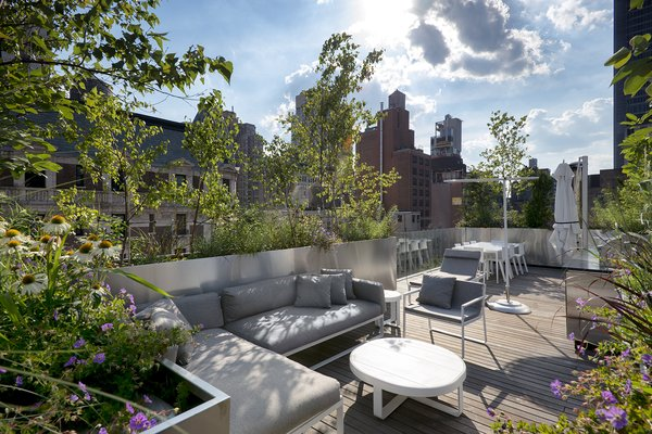 Connected by an exterior stone staircase, the rooftop level offers seating and dining areas and an outdoor kitchen.
