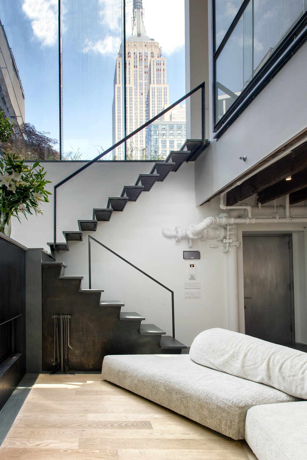 A blackened steel staircase by Delform leads to the upper level. A tall glass clerestory frames views of the Empire State Building and reinforces the indoor/outdoor motif Tagged: Living Room, Sofa, Light Hardwood Floor, and Ceiling Lighting.  Photo 4 of 10 in A Rooftop Addition on a 19th-Century Building Suits a Growing Family's Needs