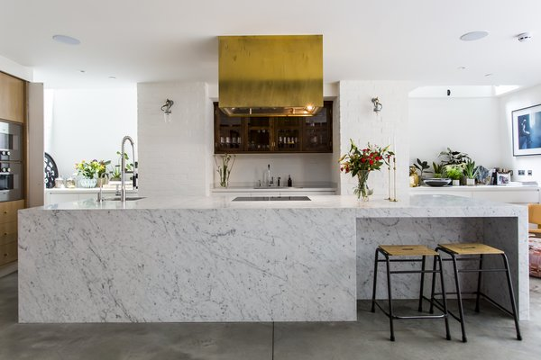 Brass finishings and an eye-catching range hood contrast with cool Carrara marble.