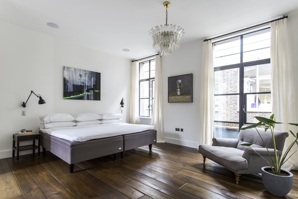 Four bedrooms on the upper level feature wood floors, modern art, and ceiling beams, while the master bedroom on the third floor (pictured here) enjoys an ensuite bathroom and private terrace. On the rooftop, another bronze-clad terrace supplies a barbecue and city views.