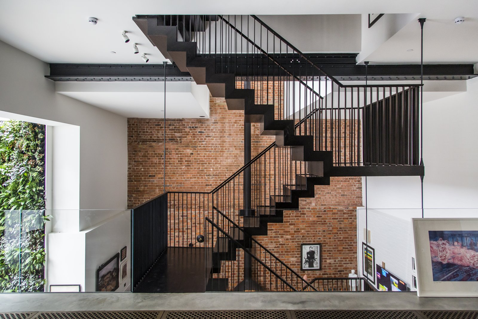 Staircase, Metal Railing, and Metal Tread Entering the apartment from the street level, guests meet a dramatic, three-story atrium and a feature staircase. A glass balustrade heightens the effect.  Photo 2 of 8 in Stay in a Converted Victorian Cooperage in London