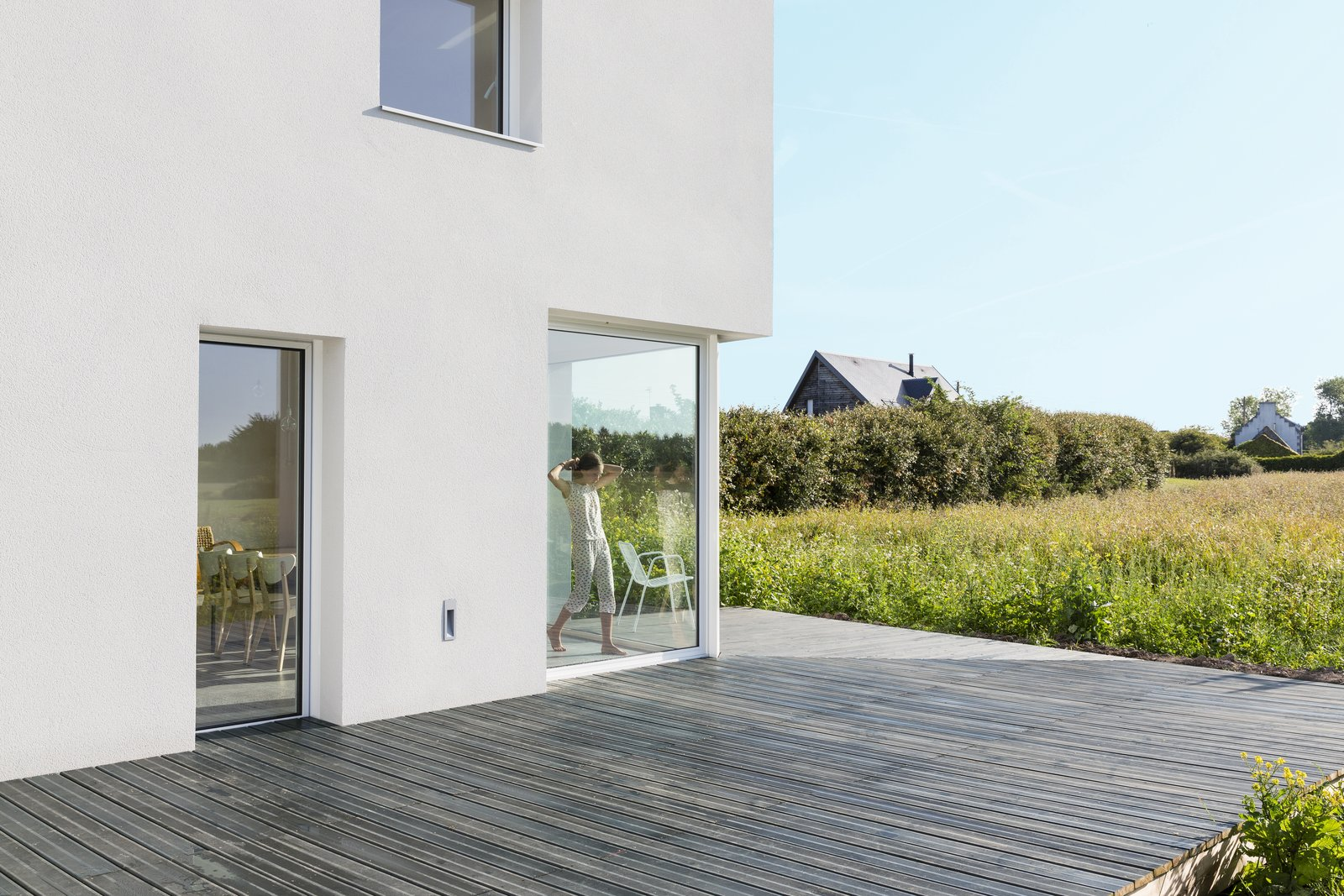 Sliding glass panels lead onto to a generous deck, which lays ensconced in the field.  Photo 8 of 10 in Framing the Landscape and Capturing Light, a Photographer's Home and Studio Echoes His Work