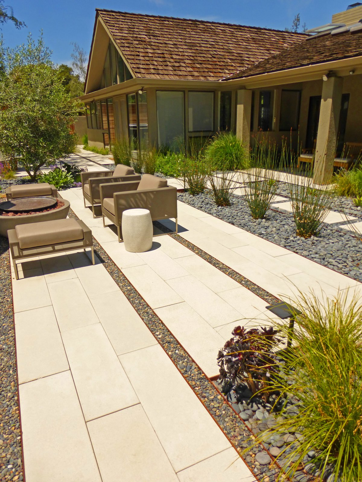 A private residence in Stanford, California, enjoys a varied patio landscape.  Photo 3 of 8 in Drawing the Line: Concrete Pavers That Advance Architectural Design