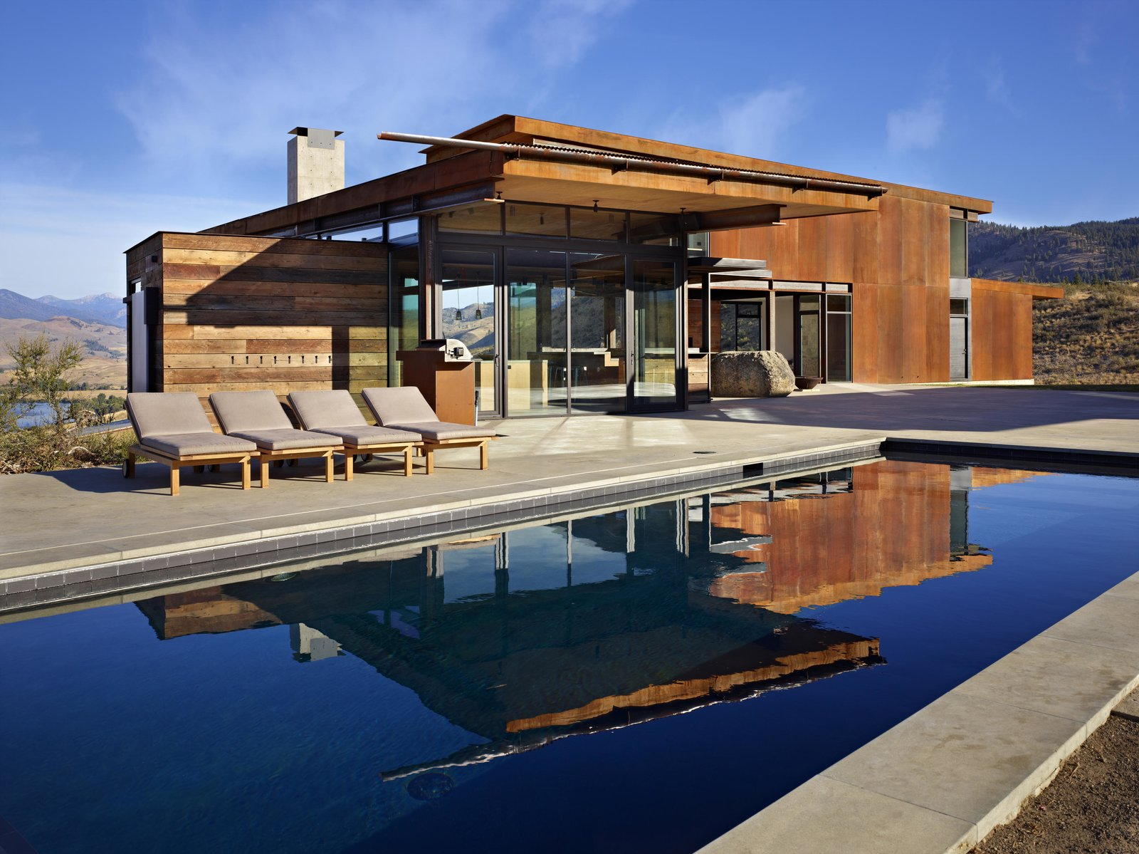 Outdoor, Large, Large, Concrete, Concrete, and Desert In the summer months, the pool provides a welcome respite from the heat.  Outdoor Desert Concrete Photos from A Steel-and-Glass Compound Is One Family's Launchpad For Adventure