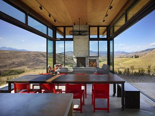 The living room features glass walls that open up to the scenery, eliminating the barrier between interior and exterior.